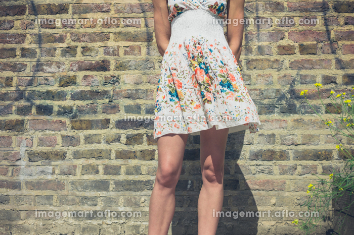 A young woman wearing a summer dress is standing by a brick wall outside on a sunny dayの販売画像