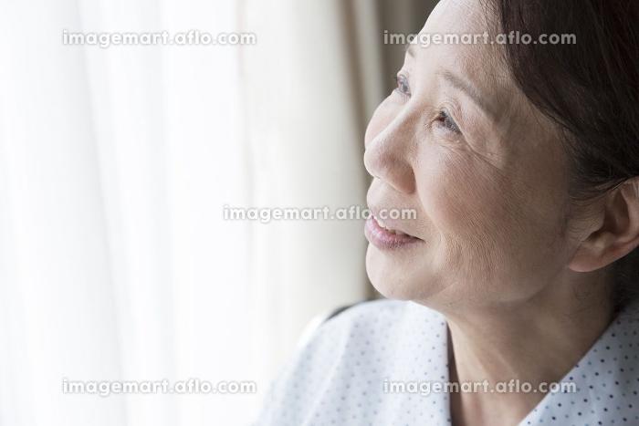窓の外を見つめるシニア女性の販売画像