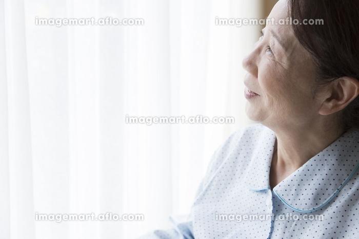 窓の外を見つめるシニア女性