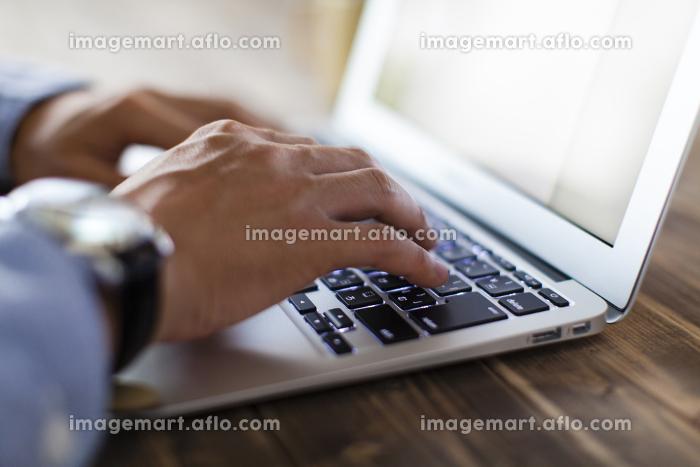 ノートパソコンで仕事をする男性の販売画像
