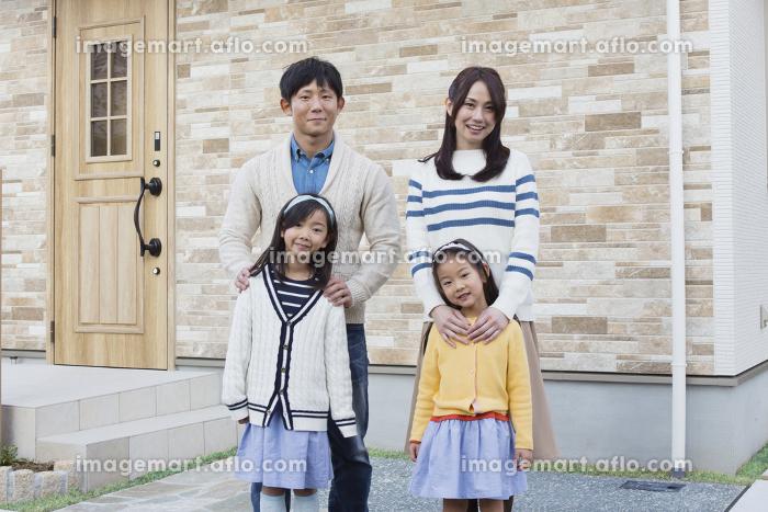 マイホームの前に立つ家族の販売画像