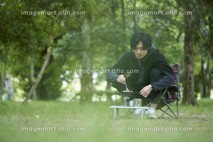 一人キャンプで料理をする若い日本人の男性の販売画像