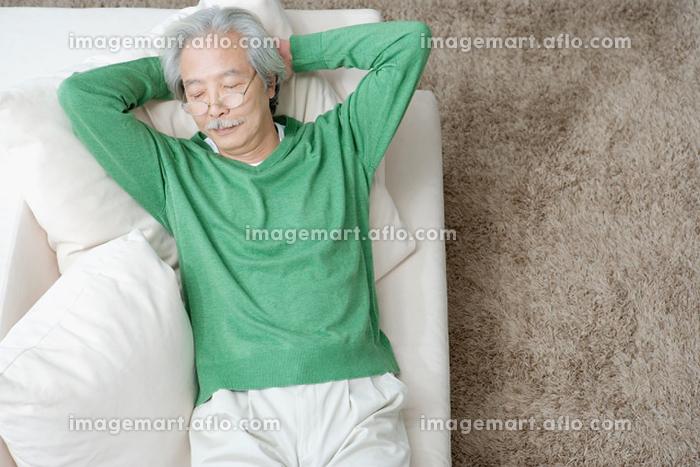 ソファでくつろぐシニアの日本人男性の販売画像