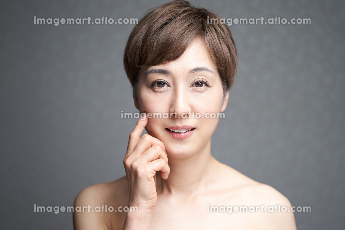 頬のハリを確かめる中年の日本人女性の販売画像