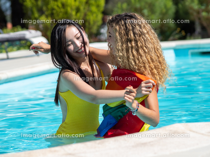 Stockphoto of two girls of different ethnicities in the water of a swimming pool with an lgtb flag attached to the waist of one of the girls. Lifestyleの販売画像