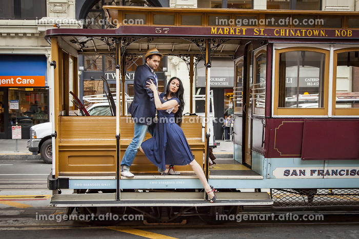 millenial couple dancing on a cable car in San Francisco.の販売画像