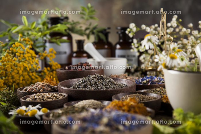 Natural medicine, herbs, mortar on wooden table backgroundの販売画像