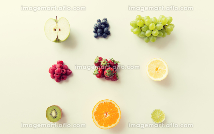 ripe fruits and berries on white surfaceの販売画像