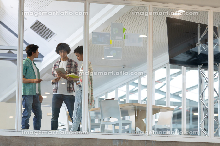 Side view of diverse businessmen discussing over documents in the modern officeの販売画像