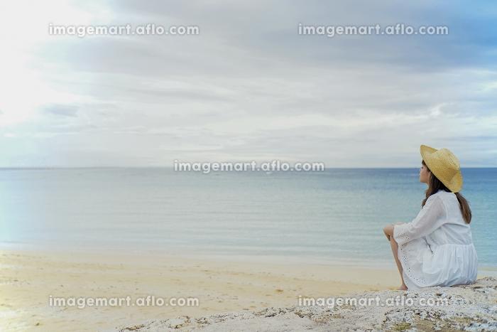 海辺の岩に座る日本人女性の販売画像