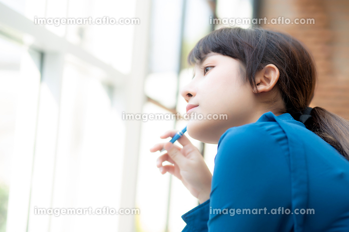 Beautiful portrait young asian woman writer smiling thinking ideの販売画像