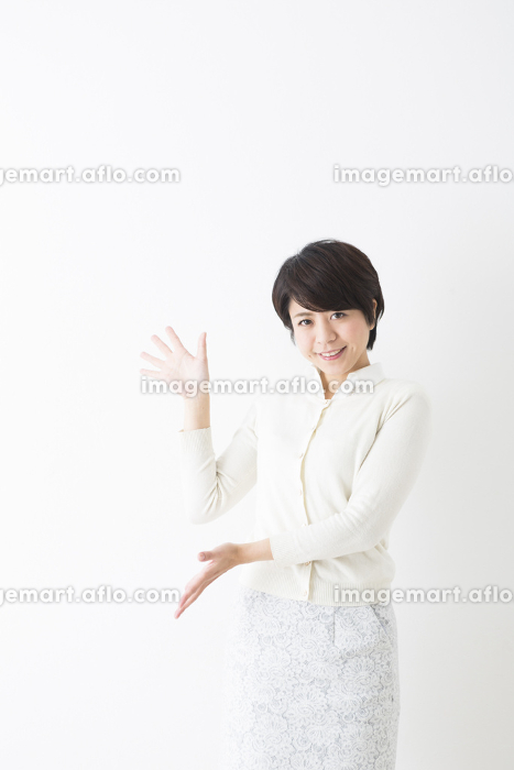 カメラ目線で案内のポーズをとる女性