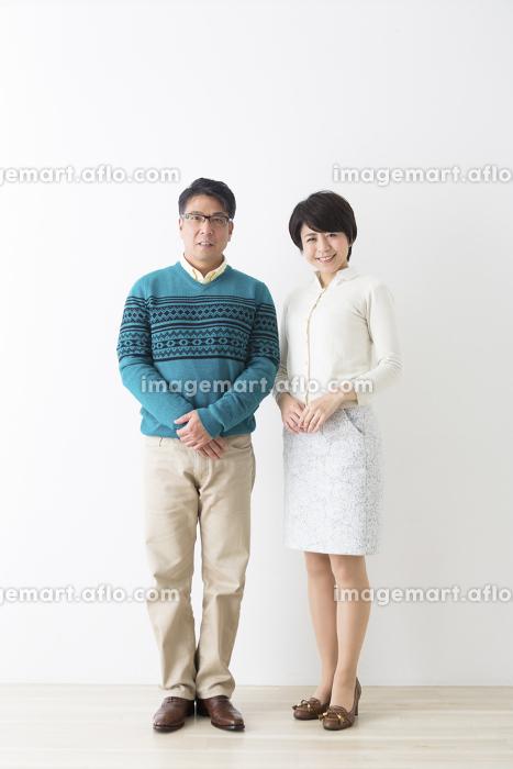 カメラ目線で並んで立つ夫婦の販売画像