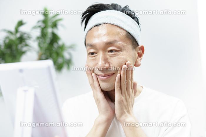 部屋でスキンケアをする男性の販売画像