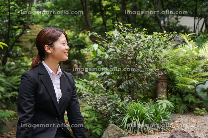 笑顔で外を歩くビジネスウーマンの販売画像