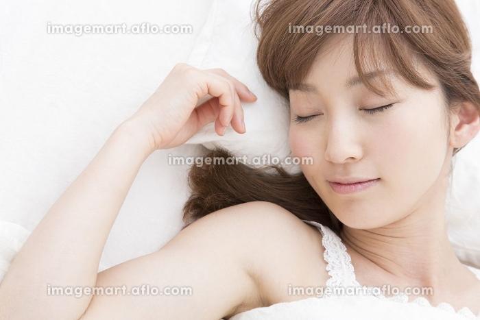 ベッドで眠る女性の販売画像