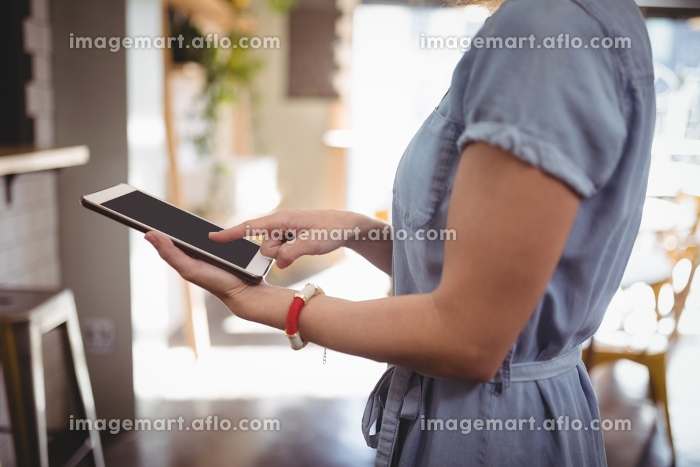 Midsection of woman scrolling digital tabletの販売画像
