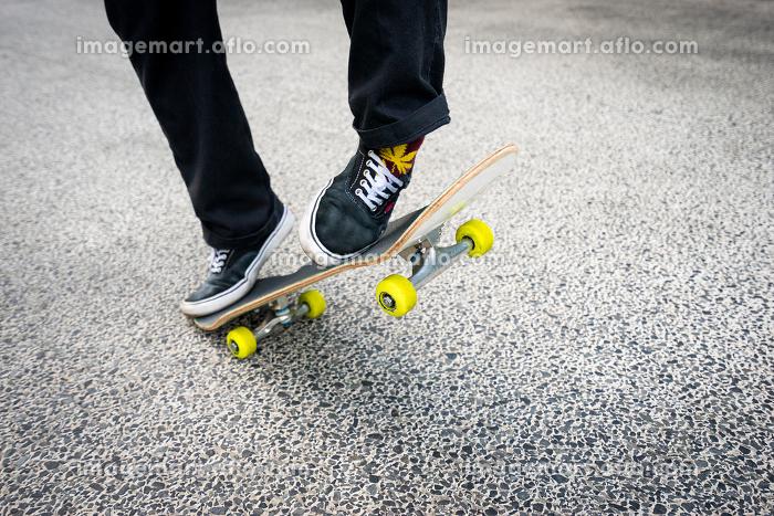 スケートボードにのる男性の足元の販売画像