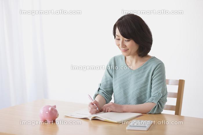 家計簿をつける40代日本人女性の販売画像