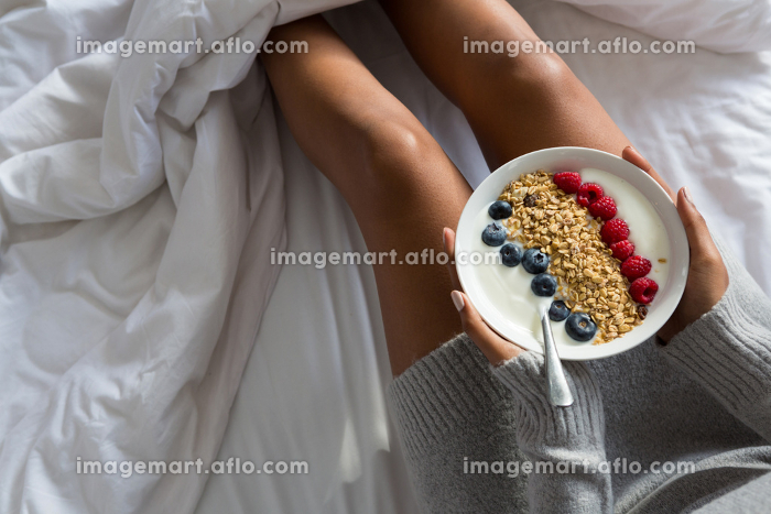 Mid section of woman having breakfast on bed