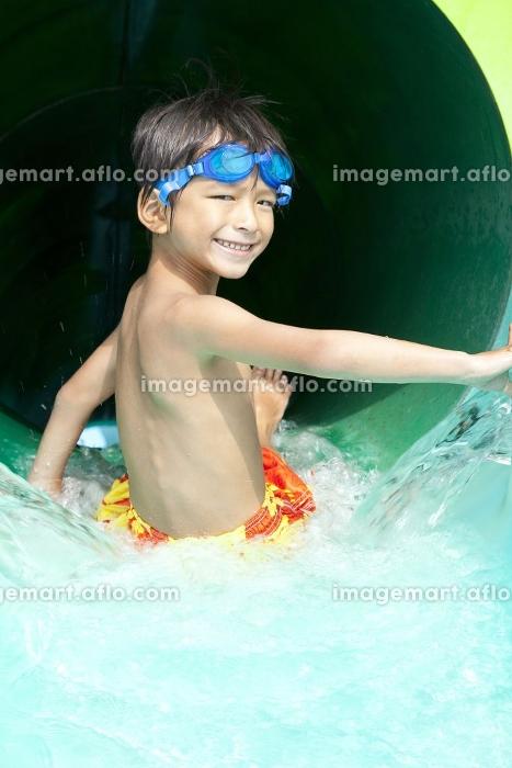 ウォータースライダーで遊ぶ水着姿の男の子