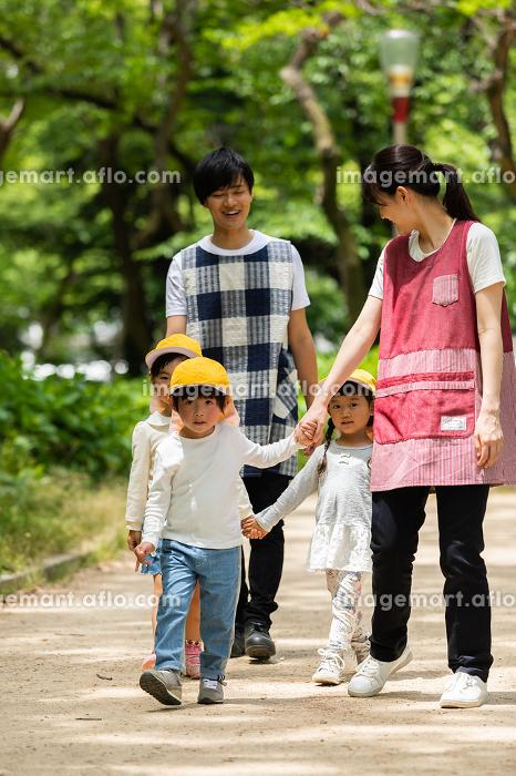 公園を散歩する保育士と園児