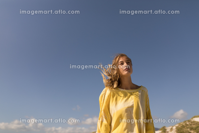 Low angle view of beautiful young woman walking on beach in the sunshineの販売画像