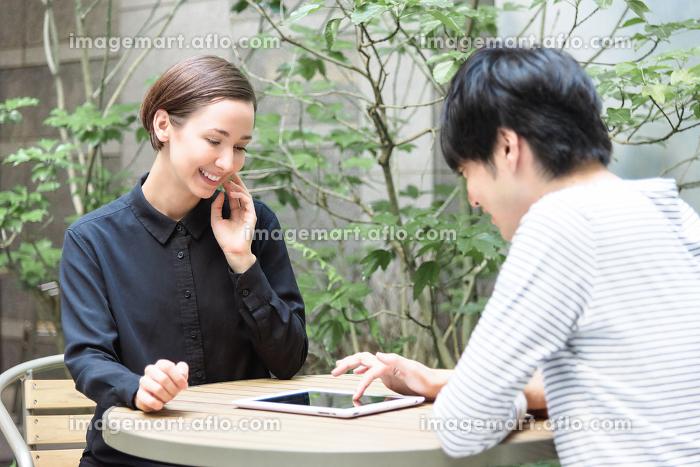 テラスでタブレットPCを使う外国人の男女の販売画像