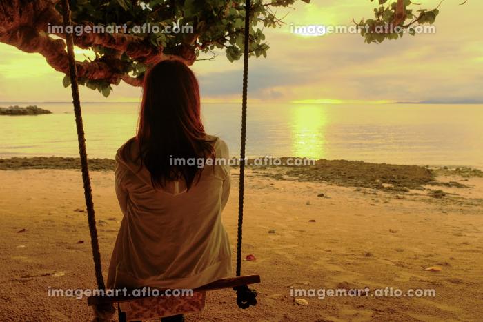 海辺のブランコに座る女性の販売画像
