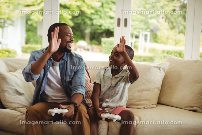 Father and son giving high five to each other while playing video gameの販売画像