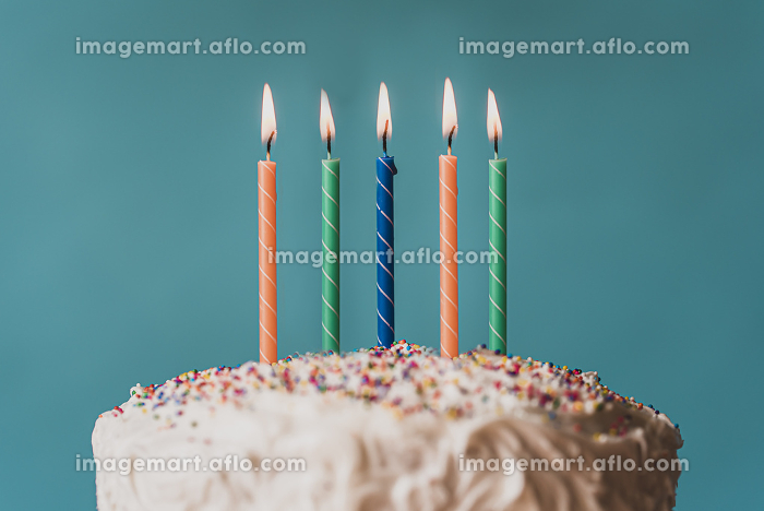 Lit candles on top of a birthday cake against blue background.の販売画像