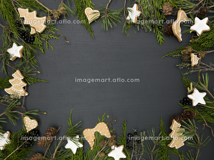 christmas background with frame with white stars, and cookies, green branches and other christmas items on blackboard