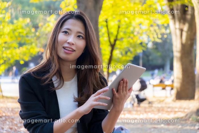 【東京都】屋外でタブレットを操作する女性【2020年 紅葉】の販売画像