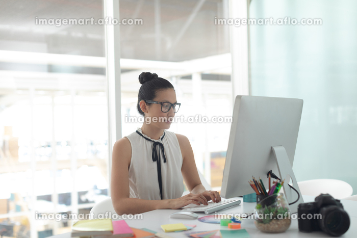 Front view of Asian female graphic designer working on computer at desk in a modern officeの販売画像