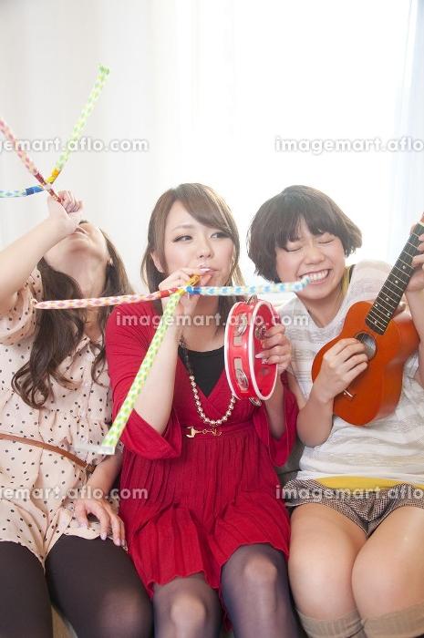 楽器を盛って騒ぐ女性3人の販売画像