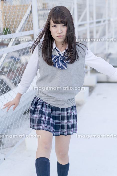 学校の屋上で片足を上げる女子高生