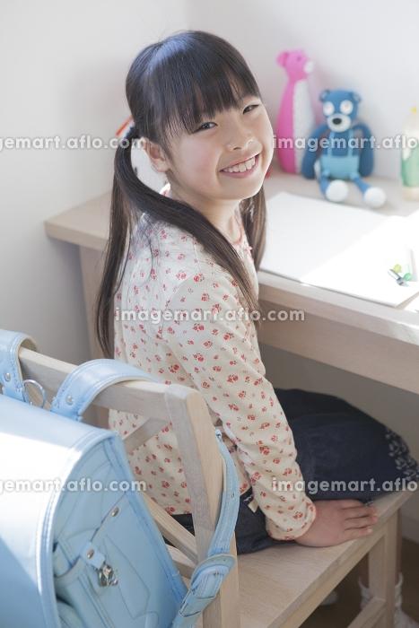 椅子に座る小学生の女の子