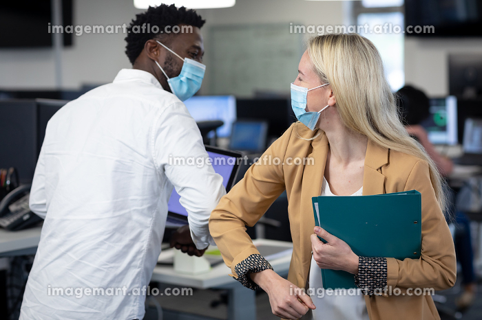 African American man and Caucasian woman in a modern office wearing face masks greeting each other by touching elbows. Hygiene and social distancing in workplace during Coronavirus Covid 19 pandemic.の販売画像