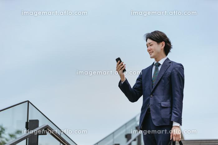 IoTのイメージ|通勤先から家の家電を操作する男性の販売画像