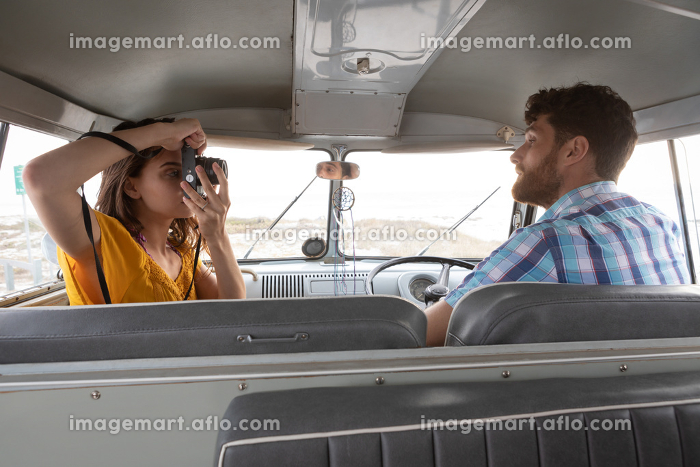 Side view of caucasian woman taking photo of a Caucasian man with digital camera in camper van at beachの販売画像