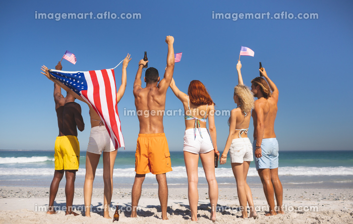 Rear view of diverse friends raising their hands on the beach while holding american flagの販売画像