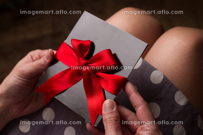 Woman hands holding a black paper card with red textile ribbonの販売画像