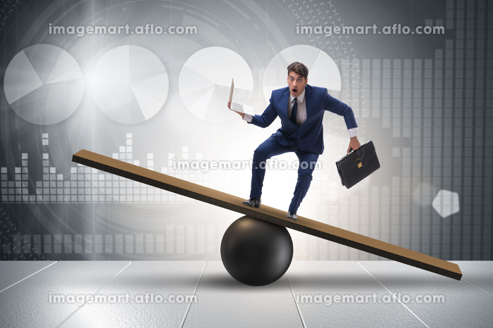 Businessman trying to balance on ball and seesaw. The businessman trying to balance on ball and seesawの販売画像