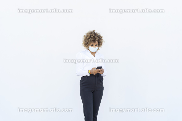 beautiful executive afro sending a message from her smartphoneの販売画像