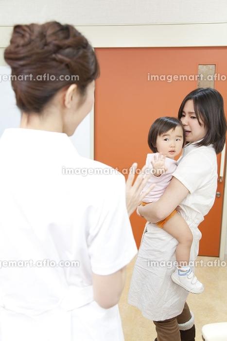 手を振る看護師と母子の販売画像