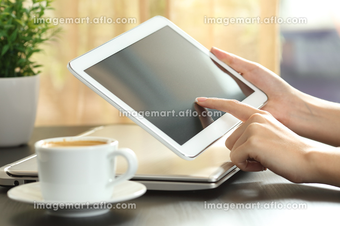 Woman hands touching a tablet screen on a tableの販売画像