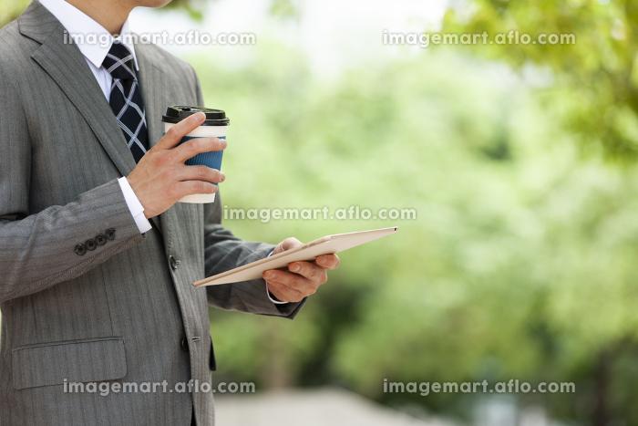 タブレットPCを見ているビジネスマンの販売画像