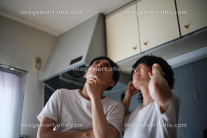 上の階の騒音に悩むカップルの販売画像