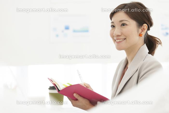 手帳を持っている笑顔のビジネスウーマンの販売画像
