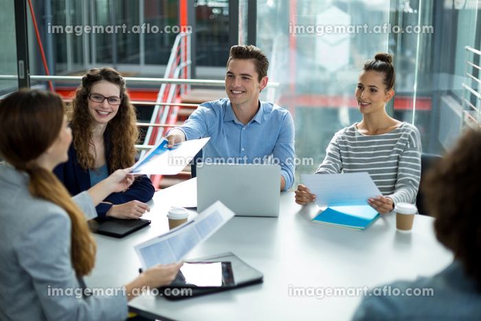 Smiling business team discussing in a meetingの販売画像